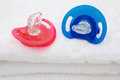 Red and blue pacifiers on white towel Royalty Free Stock Photography