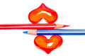 Red and blue pencils with romantic hearts conceptual image coloured to signify the sexes placed together between two valentine on Royalty Free Stock Photography