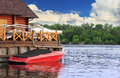 Red boat docked over picturesque cloudy river scape Royalty Free Stock Photography