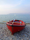 Red boat on rocky beach Royalty Free Stock Photo