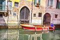Red boat Venice scenic old streets water canal. Italian Lagoon