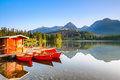 Red boats moored at wooden house on a lake.