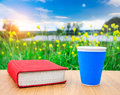 Red book and cup of hot coffee on the wooden table among of the beautiful green flower meadows and blue lake at the sunset. Royalty Free Stock Photo