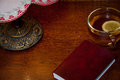 Red book, cup with tea and old vintage lamp on wooden background table at home in the evening. Horizontal view. Space for text. Royalty Free Stock Photo