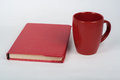 Red book and cup on a white table. Copy space for text.