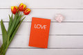 The red book Love lies on a white table. Flowers tulips and gift Royalty Free Stock Photo