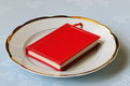 Red book on white chinaware with golden edging Stock Photography