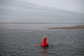 Red bouy on ocean with sand plate in background Stock Photography