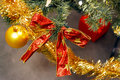 Red bow and christmas balls on fir tree with golden Stock Photos