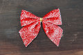 Red bow snowy on a wooden background Royalty Free Stock Image