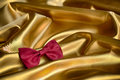 Red bow tie ties on golden cloth Stock Image