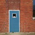 Red Brick Building Exterior Wall and Blue Door Background. Royalty Free Stock Photo