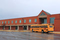 Red brick school building yellow school bus front ready transporting students to home drop off Royalty Free Stock Photography