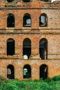 Red brick wall of abandoned building with arched windows Royalty Free Stock Photo