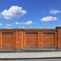 Red brick wall with blue sky and sidewalk Royalty Free Stock Photography