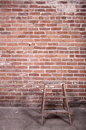 Red brick wall and ladder Stock Photo