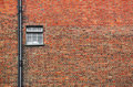 Red brick wall with small window Stock Images