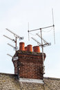 Red bricks chimney and tv antennas on the tiled roof Royalty Free Stock Images