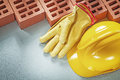 Red bricks safety gloves hard hat on concrete surface top view b Royalty Free Stock Photo