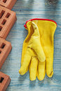 Red bricks safety gloves on wooden board top view building conce Royalty Free Stock Photo
