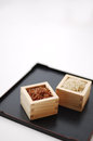 Red and brown rice in square containers on white background Royalty Free Stock Photos