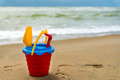 Red bucket with a shovel, a rake and a net on the beach Royalty Free Stock Photo