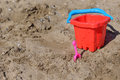 Red bucket and small pink shovel in the wet sand on the beach in Royalty Free Stock Photo