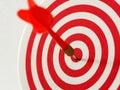 Red bullseye dart arrow hitting target center of dartboard. Concept of success, target, goal, achievement. Royalty Free Stock Photo