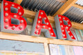 Red bulp letters on the wall saying bar with bulps wooden horizontal Stock Image