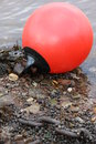 Red buoy on beach pebble Stock Photo