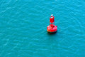 Red buoy a bright floating in a blue ocean Royalty Free Stock Photo