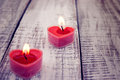 Red burning heart shaped candles on rustic white wooden table. Royalty Free Stock Photo