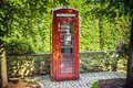 Red callbox callback in a park with green plants Royalty Free Stock Photography
