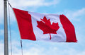Red canadian flag fluttering in the wind on blue sky