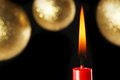 Red candle and baubles burning against a background of de focussed gold christmas Stock Image