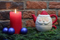Red candle, blue christmas balls and Santa Claus teapot Royalty Free Stock Photo