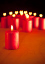 Red candle burning quietly with similar candles on background with hearts for flames symbol of season for peace and love Stock Image