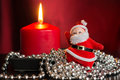 Red candle with a decor from silver balls and toy santa claus close up Stock Image