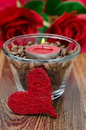 Red candle in a glass cup with coffee beans and decorative heart Royalty Free Stock Photography