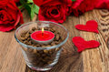 Red candle in a glass cup with coffee beans, roses and hearts Royalty Free Stock Photo