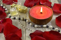Red candle with jewelry big and rose petals on wood Stock Image