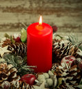 Red candle lit and pinecones for Christmas Royalty Free Stock Photo
