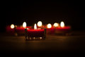 Red candles burning in darkness on black background Royalty Free Stock Photography