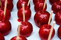Red candy apples with stuck bee to the glaze photographed on white paper as a background Stock Photos