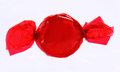 Red candy in wrapper on white background hard plastic reflective Stock Image