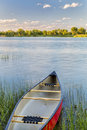 Red canoe on lake ready for paddling a calm with a green grass summer concept Royalty Free Stock Photos