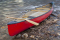 Red canoe with a paddle wooden on shore of shallow fast river Royalty Free Stock Photos