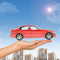 Red car above businesswomans hand with cityscape on blue sky background Royalty Free Stock Image