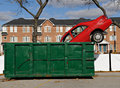 Red car and green dumpster Stock Image