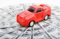 Red car over lot dollar bills Royalty Free Stock Photo